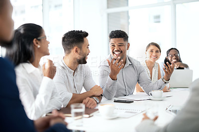Buy stock photo Shot of a young businessman having a meeting with his colleagues in a boardroom