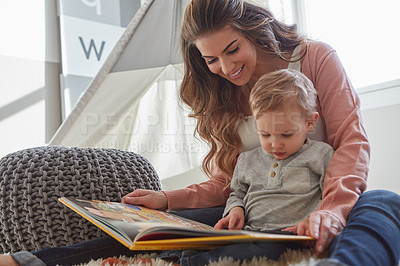 Buy stock photo Shot of a woman reading to her toddler son at home