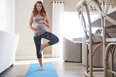 Buy stock photo Shot of a pregnant young woman practicing the tree pose during a yoga routine at home