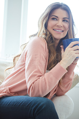 Buy stock photo Shot of a beautiful young woman having coffee while relaxing at home