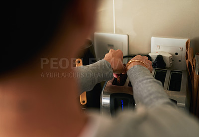 Buy stock photo Cropped shot of an unrecognizable woman putting bread in the toaster