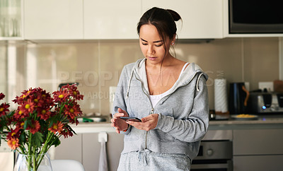 Buy stock photo Shot of a young woman using her cellphone at home