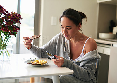 Buy stock photo Cropped shot of a woman using her cellphone while having breakfast at home