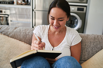 Buy stock photo Cropped shot of a young woman writing in a notebook while sitting at home