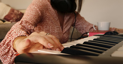 Buy stock photo Shot of an unrecognisable woman playing music on a keyboard at home