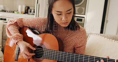 Buy stock photo Shot of a young woman playing a guitar on the sofa at home