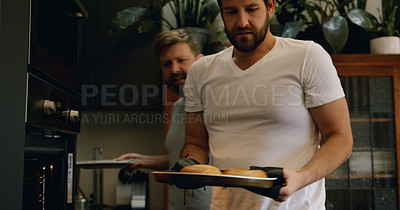 Buy stock photo Shot of a mature couple baking bagels for breakfast at home