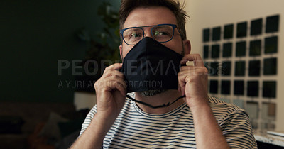 Buy stock photo Shot of a mature man putting on a face mask at home