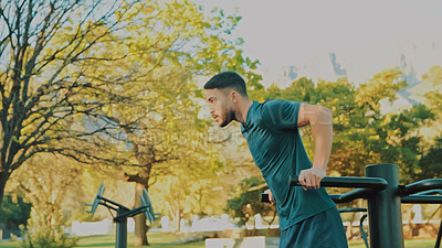 Buy stock photo Shot of a man using outdoor gym equipment at the park