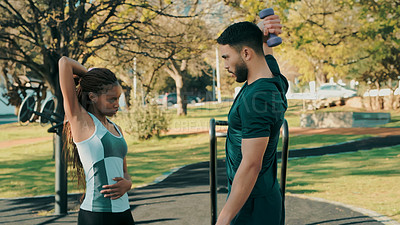 Buy stock photo Shot of a man coaching a woman through her workout at the park