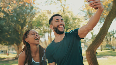 Buy stock photo Shot of a young couple taking selfies while out exercising at the park