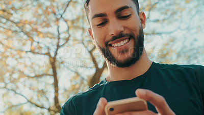 Buy stock photo of a man using his cellphone while out for a run at the park