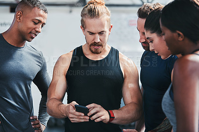 Buy stock photo Cropped shot of a group of young athletes looking at a cellphone while standing in the gym