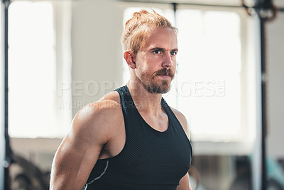 Buy stock photo Cropped shot of a handsome young man working out in the gym