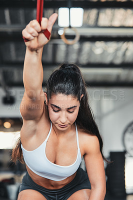 Buy stock photo Cropped shot of an attractive young female athlete working out with a resistant band in the gym