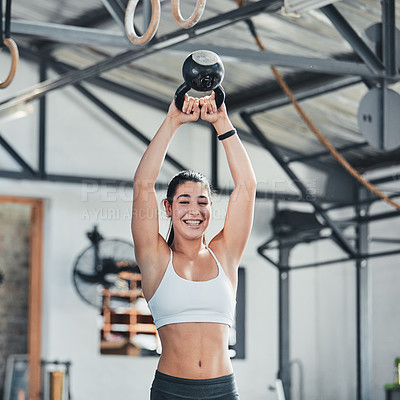 Buy stock photo Cropped portrait of an attractive young female athlete working out with a kettle bell in the gym