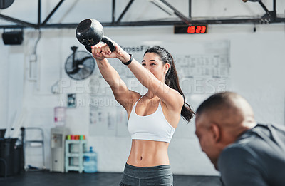 Buy stock photo Cropped shot of an attractive young female athlete working out with a kettle bell in the gym