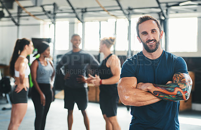 Buy stock photo Cropped portrait of a handsome young male athlete standing with his arms folded in the gym with other gym-goers in the background