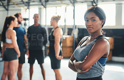 Buy stock photo Cropped portrait of an attractive young female athlete standing with her arms folded in the gym with other gym-goers in the background