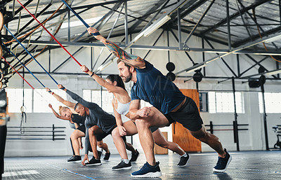 Buy stock photo Full length shot of a group of young athletes going through their warmup routine in the gym