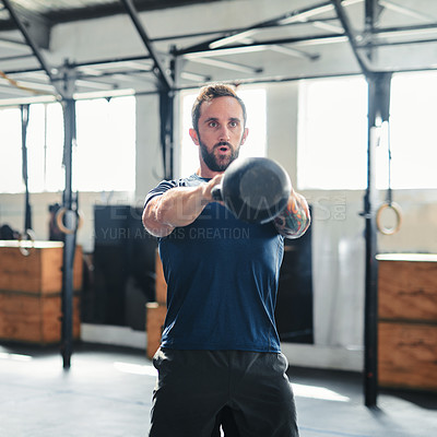 Buy stock photo Cropped shot of a handsome young male athlete working out with a kettle bell in the gym