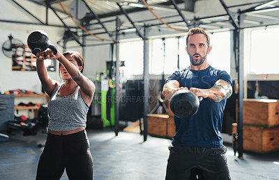 Buy stock photo Shot of two people working out using kettle bells  at the gym