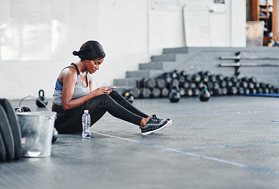 Buy stock photo Shot of a young woman using her cellphone while sitting at the gym