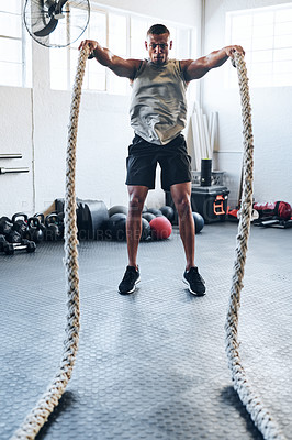 Buy stock photo Shot of a muscular young man working out with battle ropes at the gym