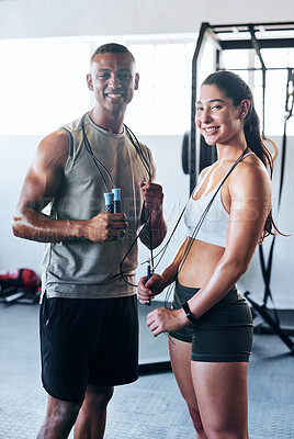 Buy stock photo Portrait shot of two young athletes using skipping ropes while working out at the gym