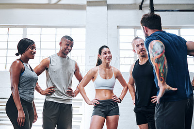 Buy stock photo Shot of a group of young people talking while standing together at the gym