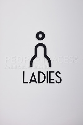 Buy stock photo Shot of a female restroom sign on the wall of a building