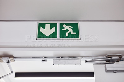 Buy stock photo Shot of a fire exit sign mounted on a wall in a building