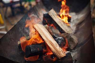 Buy stock photo Shot of a fire burning wooden logs at a campsite out in nature