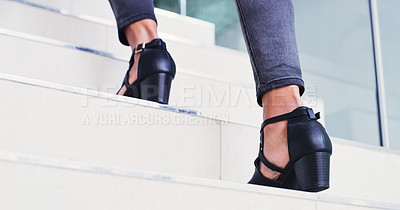 Buy stock photo Shot of a businesswoman wearing heels while walking up a staircase