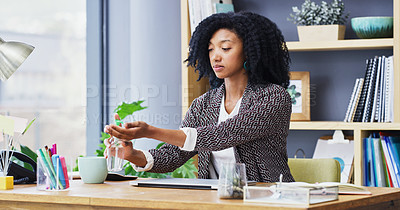 Buy stock photo Cropped shot of a businesswoman sanitising her hands while sitting at her desk