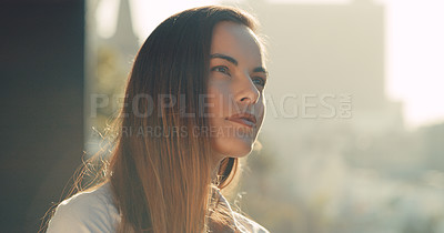 Buy stock photo Cropped shot of a beautiful young woman looking thoughtful while standing outside in the city