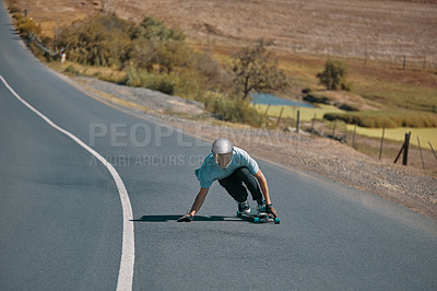 Buy stock photo Shot of a man skating with his long board along a road