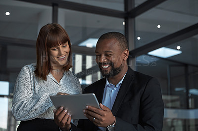 Buy stock photo Shot of two businesspeople working together on a digital tablet in an office at night
