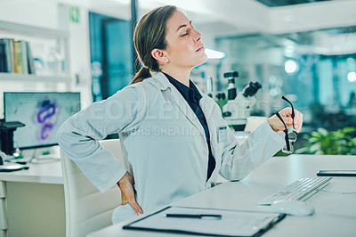 Buy stock photo Shot of a scientist experiencing back pain while conducting research in a laboratory