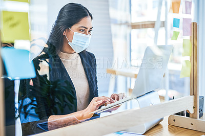 Buy stock photo Shot of a young businesswoman wearing a face mask while working on a laptop in an office