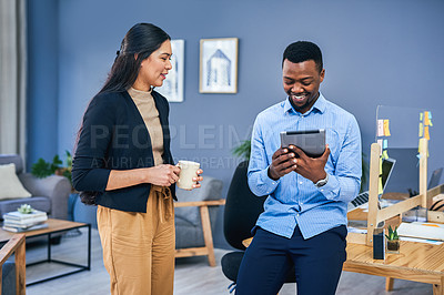 Buy stock photo Shot of two businesspeople having a discussion while using a digital tablet together in an office