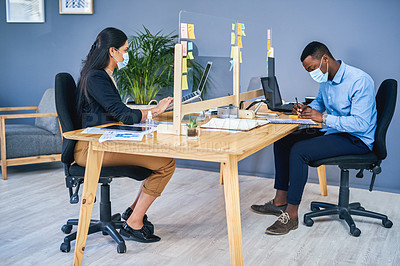 Buy stock photo Shot of two businesspeople wearing face masks while working in an office