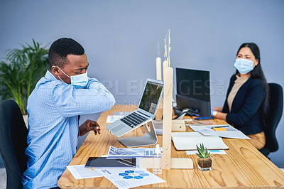 Buy stock photo Shot of a young businessman sneezing into his elbow while working in an office with a colleague