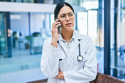 Buy stock photo Shot of a young doctor looking stressed out while using a smartphone in a modern hospital