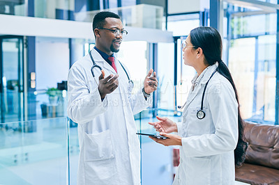 Buy stock photo Shot of two young doctors using a digital tablet during a discussion in a clinic