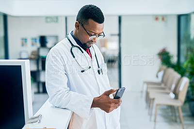 Buy stock photo Shot of a young doctor using a smartphone in a modern hospital