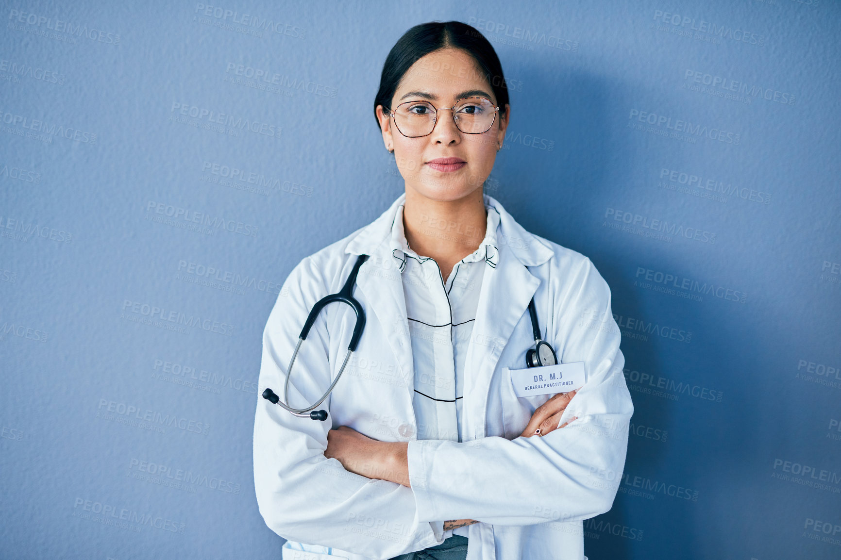 Buy stock photo Studio portrait of a confident young doctor standing against a blue background