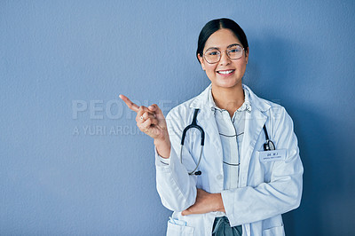 Buy stock photo Studio portrait of a confident young doctor pointing against a blue background