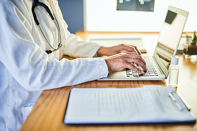 Buy stock photo Shot of a doctor using a laptop in a modern hospital