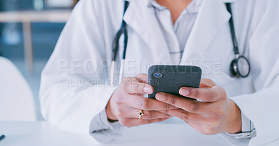 Buy stock photo Shot of a doctor using a smartphone in a modern hospital